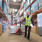Female warehouse manager holding clipboard and pulling pallet truck